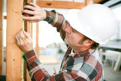 Wooden Door Frame Measured By A Workmen